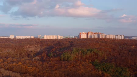 reddish : Apartments building at city skyline with autumn forest at sunset