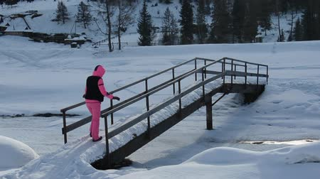 ribeiro : Tourist walking on the bridge over the creek. Cold snowy winter. Slow motion.