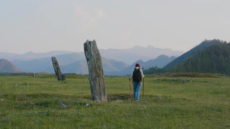 stella : Woman tourist examines ancient stone stelts of the Turkic period in the Altai mountains. Nature Park Uch-Enmek, Altai Republic, Siberia, Russia.