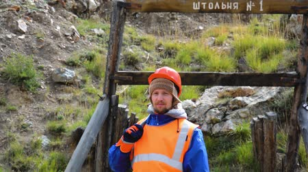 "archeologický : Mining engineer, a geologist in the protective reflective vest, gloves and helmet, with hammer in hand. Against the background of the release of rocks. The inscription Gallery â""– 1 Dostupné videozáznamy"