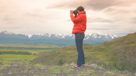 woman in a red jacket, jeans with a camera. Woman photographer taking photo using DSLR camera outdoors on hike. Female hiker taking pictures outside living outdoor lifestyle in nature landscape. Стоковые видеозаписи