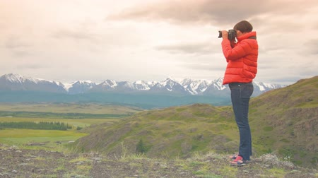 Woman photographer taking photo using DSLR camera outdoors on hike. Female hiker taking pictures outside living outdoor lifestyle in nature landscape. A woman in a red jacket, jeans with a camera.