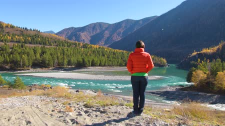 çekicilik : A woman stands by the river with a view of the mountains. Stok Video