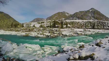 luty : Spring high water on the Katun River, Altai Mountains, Siberia, Russia. Snow and ice on the river bank. Turquoise water and blue sky. Slow motion.