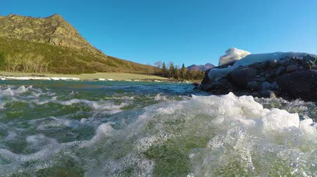 пробуждение : Spring waters in the stream, the snow lies in the valley, the sun is shining. The Altai Mountains.