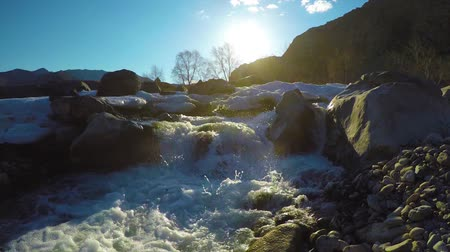 thaw : Spring waters in the stream, the snow lies in the valley, the sun is shining. The Altai Mountains.