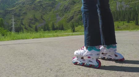 колготки : Roller-skater. Close-up shot of female legs in inline skates moving on walking path. Slow motion.
