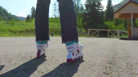 inline skating : Roller-skater. Close-up shot of female legs in inline skates moving on walking path. Slow motion.