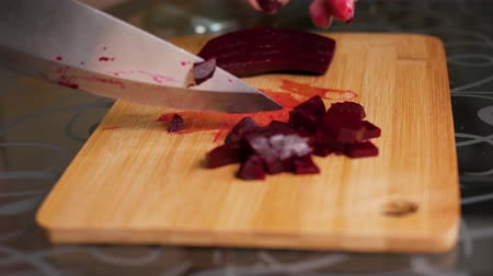 ebulição : Cutting boiled beets. Female hands are cutting on a wooden cutting board. Close-up