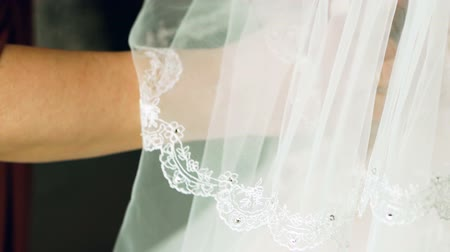 dama de honor : Mother of the bride ties her daughters wedding dress. Closeup