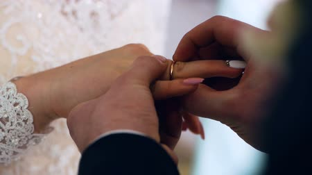 závazek : The groom hardly puts the ring on the brides finger. Closeup