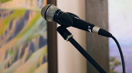 comediante : Wired dynamic microphone with a spherical protective mesh attached to the microphone stand. Close-up Archivo de Video
