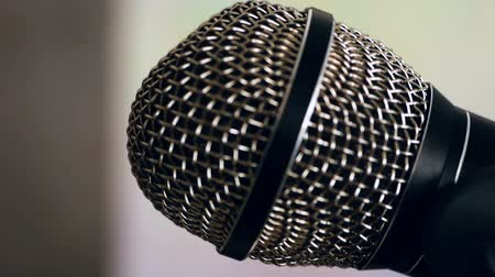 csatolt : Wired dynamic microphone with a spherical protective mesh attached to the microphone stand. Close-up Stock mozgókép
