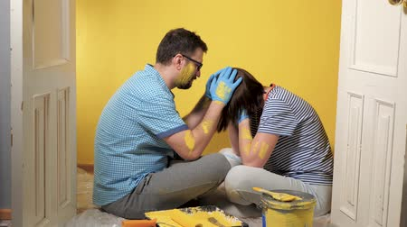 obnova : Tired couple man and woman are sitting on floor. Girl is crying with joy, and guy is trying to calm her down. Painting repair work over concept. Slow motion Dostupné videozáznamy