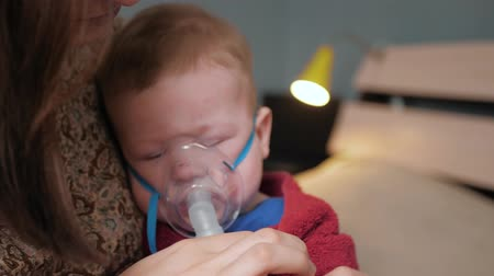compressor : Girl puts on mask for inhalation on baby and turns on nebulizer. Baby begins to cry. Slow motion and Close-up