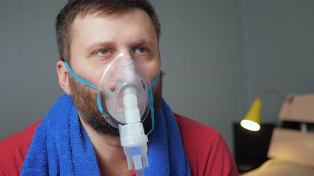 compressore : Man makes inhalation using nebulizer. Slow motion and close-up