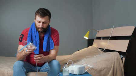 compressore : Man screws inhalation mask to nebulizer. Young man sits alone in room and fastens mask to inhaler. Slow motion and long shot Filmati Stock