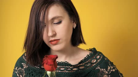 geheimnisvoll : Girl with red rose flower is looking at flower impassively on yellow backgraund. Valentine Day, February 14, birthday, anniversary, first date concept. Slow motion and close up Videos