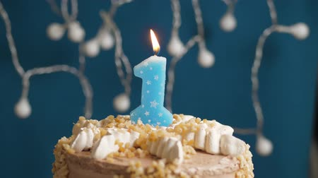 時代遅れの : Birthday cake with 1 number candle on blue backgraund. Candles blow out. Slow motion and close-up
