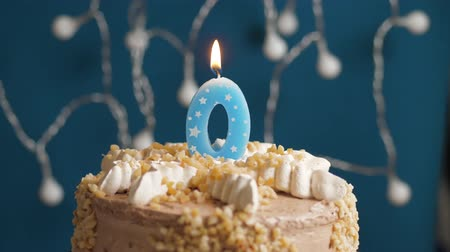 anlamlı : Birthday cake with 0 number candle on blue backgraund. Candles blow out. Slow motion and close-up Stok Video