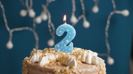 anlamlı : Birthday cake with 2 number candle on blue backgraund. Candles blow out. Slow motion and close-up
