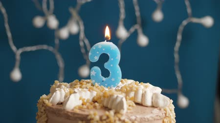 時代遅れの : Birthday cake with 3 number candle on blue backgraund. Candles blow out. Slow motion and close-up 動画素材