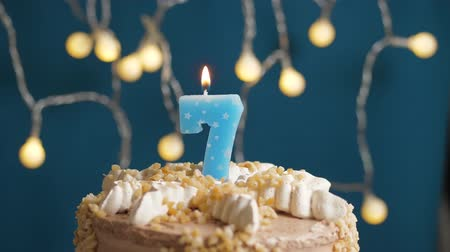 時代遅れの : Birthday cake with 7 number candle on blue backgraund. Candles blow out. Slow motion and close-up