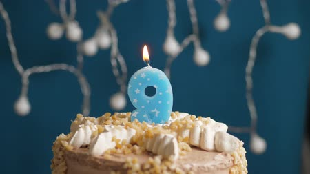 devět : Birthday cake with 9 number candle on blue backgraund. Candles blow out. Slow motion and close-up Dostupné videozáznamy