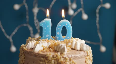dez : Birthday cake with 10 number candle on blue backgraund. Candles blow out. Slow motion and close-up