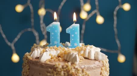 時代遅れの : Birthday cake with 11 number candle on blue backgraund. Candles blow out. Slow motion and close-up 動画素材