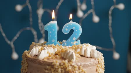 時代遅れの : Birthday cake with 12 number candle on blue backgraund. Candles blow out. Slow motion and close-up