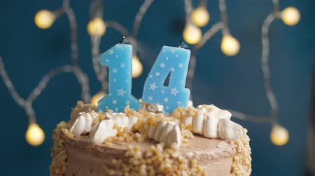 時代遅れの : Birthday cake with 14 number candle on blue backgraund. Candles blow out. Slow motion and close-up