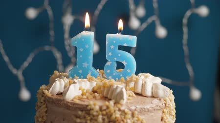 時代遅れの : Birthday cake with 15 number candle on blue backgraund. Candles blow out. Slow motion and close-up