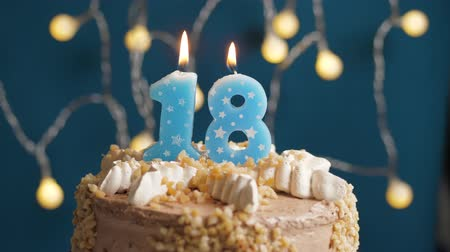 anlamlı : Birthday cake with 18 number candle on blue backgraund. Candles blow out. Slow motion and close-up