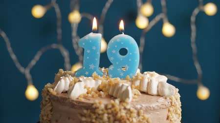 anlamlı : Birthday cake with 19 number candle on blue backgraund. Candles blow out. Slow motion and close-up