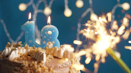 anlamlı : Birthday cake with 18 number candle and sparkler on blue backgraund. Slow motion and close-up view