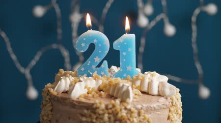 výrazný : Birthday cake with 21 number burning candle on blue backgraund. Candles blow out. Slow motion and close-up view