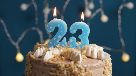 時代遅れの : Birthday cake with 23 number burning candle on blue backgraund. Candles blow out. Slow motion and close-up view