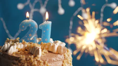 anlamlı : Birthday cake with 21 number candle and sparkler on blue backgraund. Slow motion and close-up view