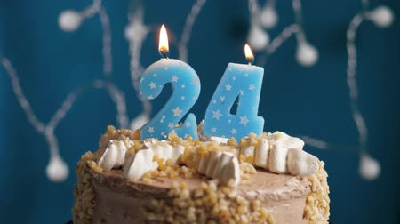 výrazný : Birthday cake with 24 number burning candle on blue backgraund. Candles blow out. Slow motion and close-up view