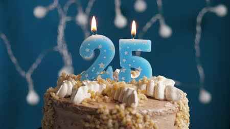 anlamlı : Birthday cake with 25 number burning candle on blue backgraund. Candles blow out. Slow motion and close-up view Stok Video
