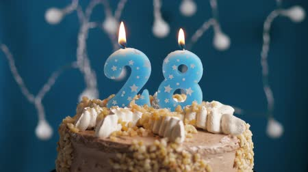 výrazný : Birthday cake with 28 number burning candle on blue backgraund. Candles blow out. Slow motion and close-up view