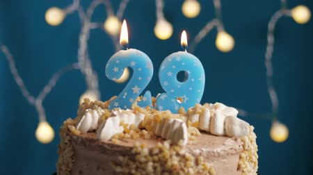 anlamlı : Birthday cake with 29 number burning candle on blue backgraund. Candles blow out. Slow motion and close-up view