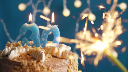 anlamlı : Birthday cake with 30 number candle and sparkler on blue backgraund. Slow motion and close-up view