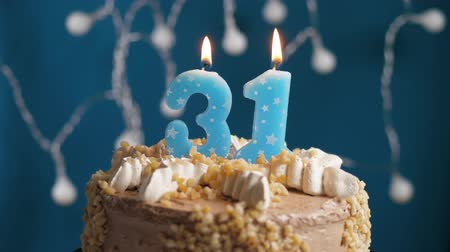 výrazný : Birthday cake with 31 number burning candle on blue backgraund. Candles blow out. Slow motion and close-up view