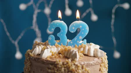 anlamlı : Birthday cake with 32 number burning candle on blue backgraund. Candles blow out. Slow motion and close-up view Stok Video