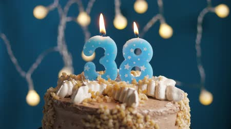 výrazný : Birthday cake with 38 number burning candle on blue backgraund. Candles blow out. Slow motion and close-up view