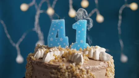 výrazný : Birthday cake with 41 number burning candle on blue backgraund. Candles blow out. Slow motion and close-up view