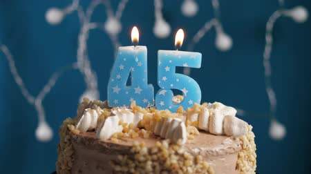 výrazný : Birthday cake with 45 number burning candle on blue backgraund. Candles blow out. Slow motion and close-up view
