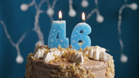 výrazný : Birthday cake with 46 number burning candle on blue backgraund. Candles blow out. Slow motion and close-up view